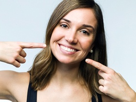 Woman pointing to her straight smile after braces.