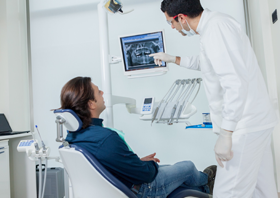 Dentist and patient looking at digital x-rays