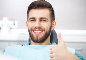 man giving thumbs up in dental chair