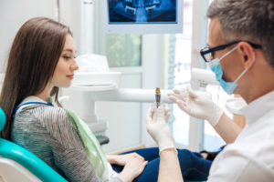 Dentist talkihng to patient about dental implants
