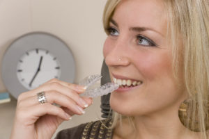 Adult woman putting in Invisalign aligner