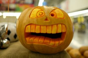orange pumpkin with a scared face carved into it